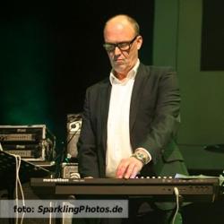 Etalageblokje voor De platenkast van Wim Dekker, interview over en met muziek. Het beeld is Wim Dekker die op het podium staat met zijn synthesizers en laptop. Foto geschoten door een fotograaf van www.SparklingPhotos.de