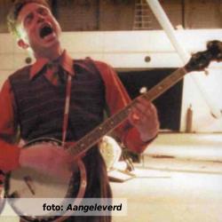 De platenkast van Robert van der Tol, interview over en met muziek. Foto toont Robert van der Tol spelend op de banjo, en zingend.